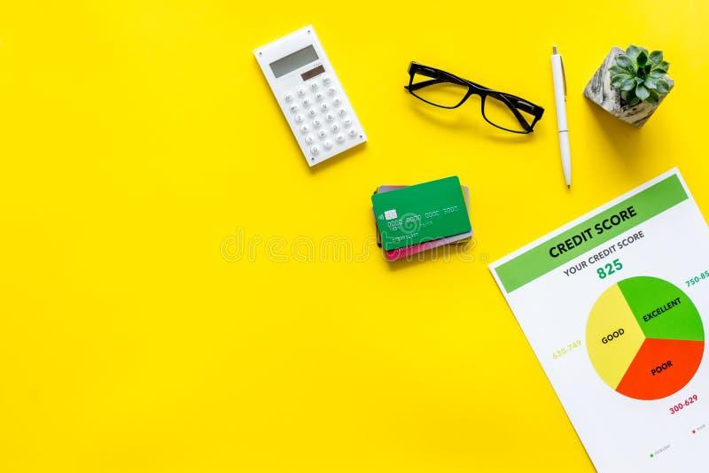 Pontuação de crédito com cartões de crédito e calculadora, vidros na zombaria amarela da opinião superior do fundo do lugar de tr foto de stock