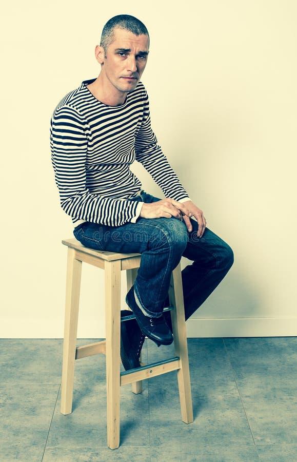 Ponury mężczyzna wyraża depresję z pasiastym puloweru obsiadaniem zdjęcie stock