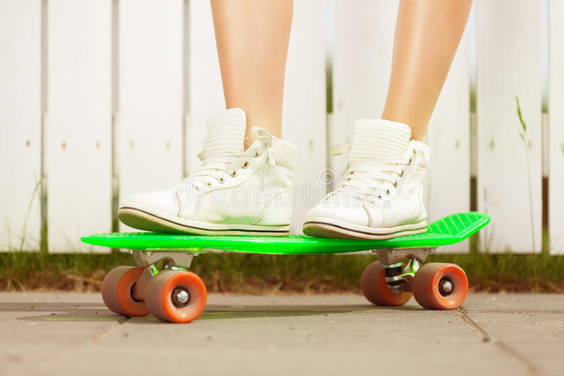 On a pony skateboard. Close-up of a woman's legs on a pony skateboard stock photos