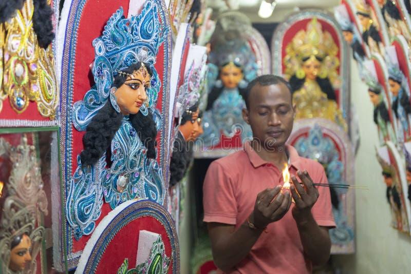 pooja的在Kumartuli,加尔各答,印度Shopowner灼烧的香火棍子 免版税库存照片