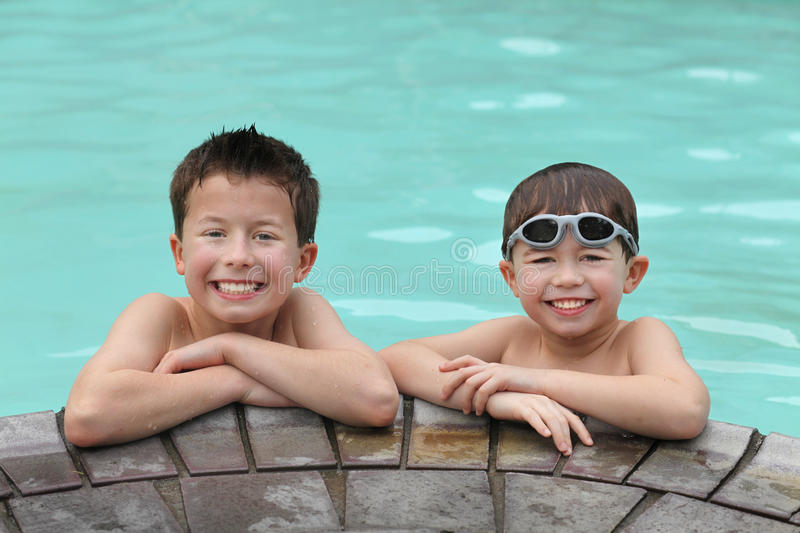 At the pool. Two cute young boys at the edge of a swimming pool stock photo