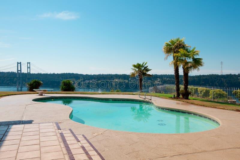 Pool aan het huis van de luxewaterkant met palmen en een mening van Na royalty-vrije stock fotografie