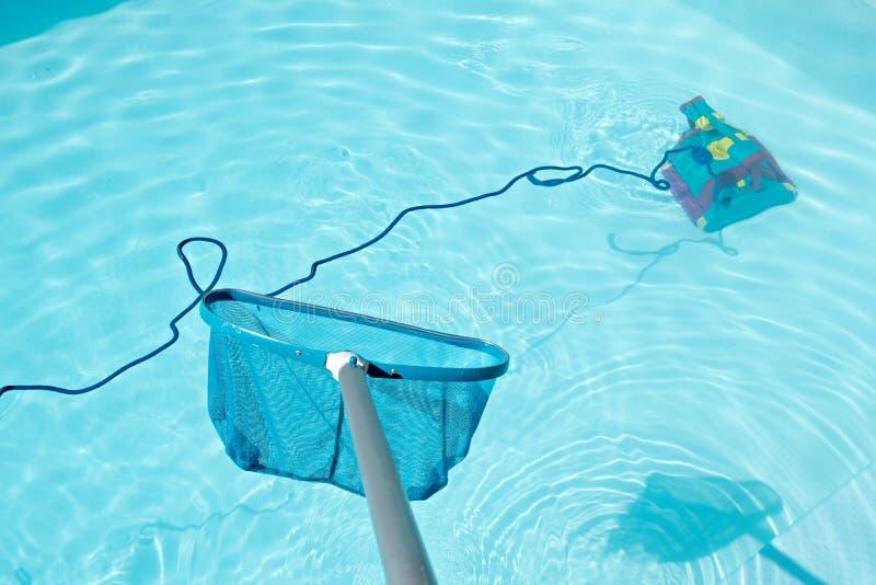 Pool-Abstreicheisen und Reinigungsroboter im Swimmingpool stockfotos