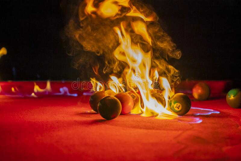 Pool Balls Are Lit On Fire While Sitting On A Pool Table In An ...