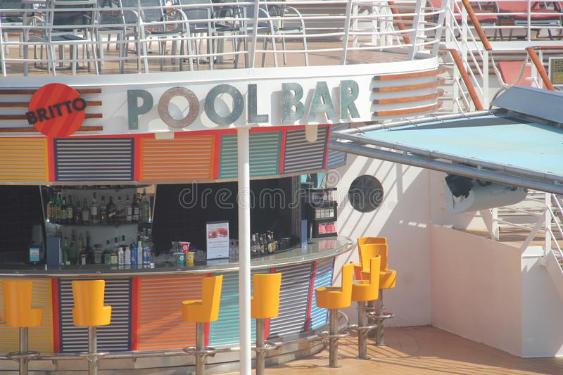 Pool Bar on a cruise. A pool bar serving alcohol and drinks, situated next to an outdoor pool on board a luxury cruise ship stock image