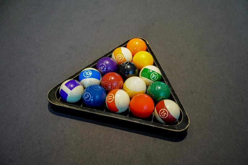 Pool billiard balls in a wooden rack on black background royalty free stock photo