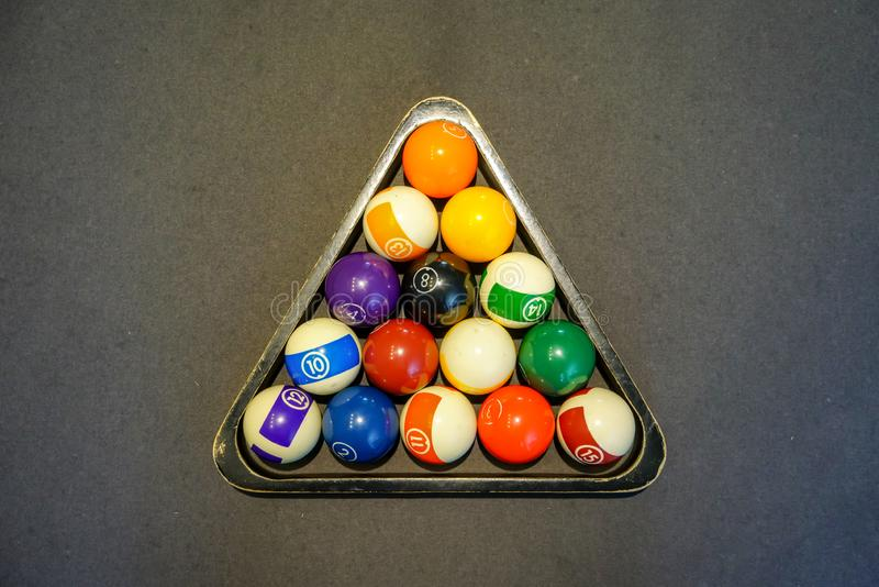 Pool billiard balls in a wooden rack on black background stock photos