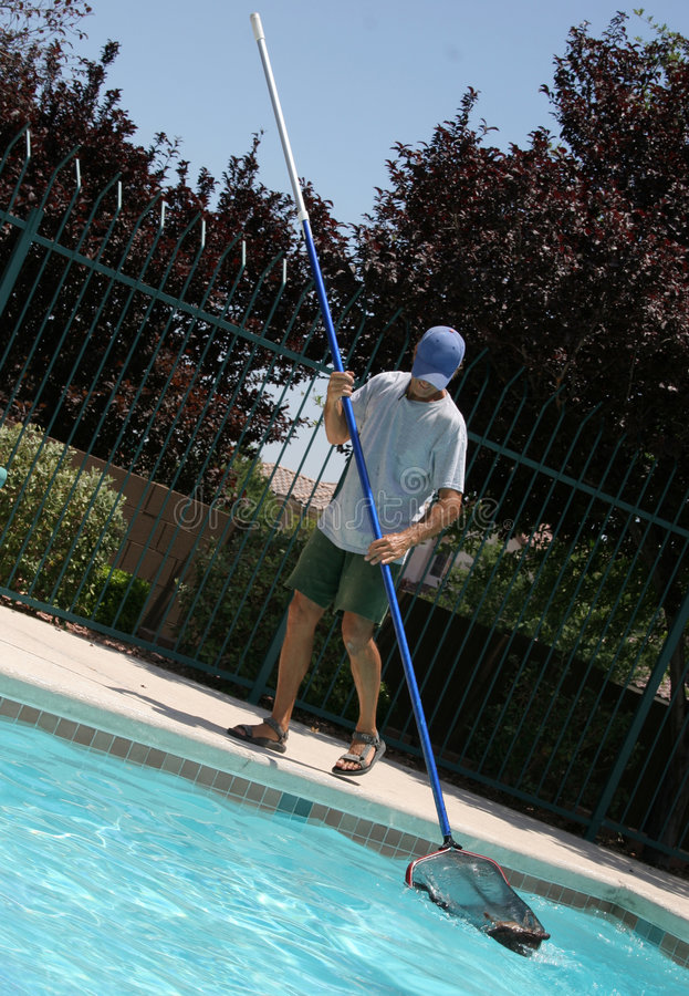 Pool Boy. Man cleaning out community pool royalty free stock photo