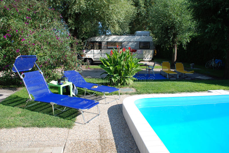 Pool at Camp Site. A swimming pool at an Hungarian tent and campervan camp site. There are several beach chairs by the side of the pool and an A-Class campervan stock photos