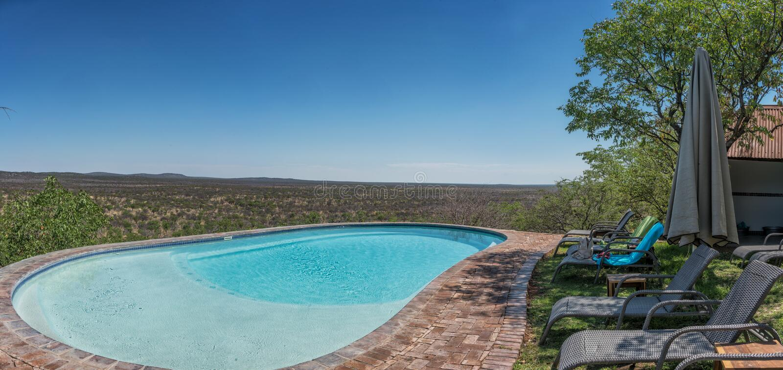 Pool with chairs overlooking the Namibian African savannah. Africa stock photos