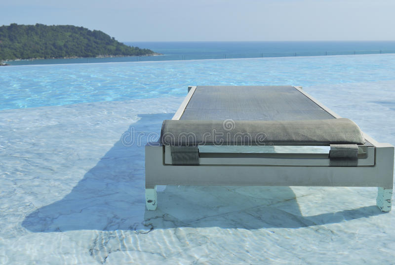 Pool chairs on swimming pool seaview and blu stock photography