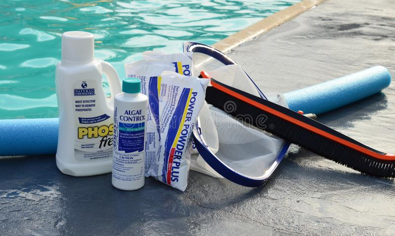 Pool chemicals by pool. A close up of a set of pool chemicals by the pool royalty free stock photography