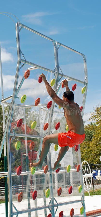 Pool Climbing Wall. African American muscular man ascends a climbing wall at a pool on a beautiful sunny day stock image