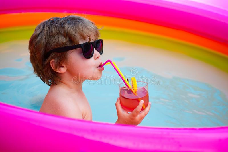 Pool and cocktail. Luxury life. Vacation breaks. Resort. Boy drinks a delicious cocktail in the pool. Child mood. royalty free stock photos