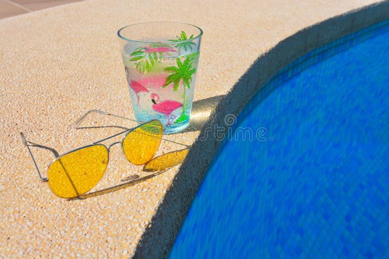 Sunglasses and a drink by the poolside stock images
