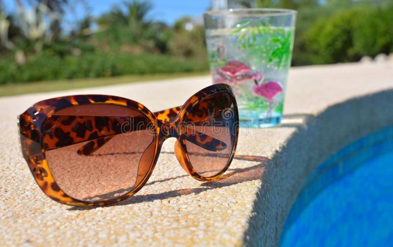 Sunglasses and a drink by the poolside royalty free stock photography