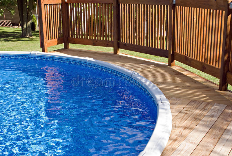 Pool Deck and Railing. Round above-ground home pool with wooden deck and railing royalty free stock photography