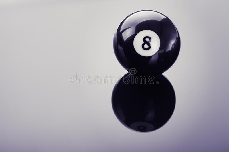 Pool eight ball on glass. A pool black eight ball shot over a dark reflective surface royalty free stock images