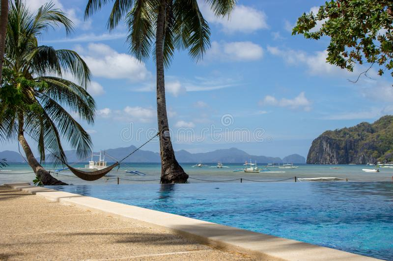Pool and empty hammock with palm trees, isles and boats on background. Tropical beach. Philippines resort landscape. royalty free stock image