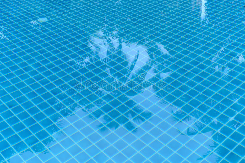 Pool Floor. Tiles floor under the pool reflex the tree royalty free stock image
