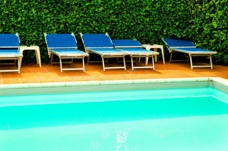 Pool in hotel. Pool with chaise-longues in hotel stock photos
