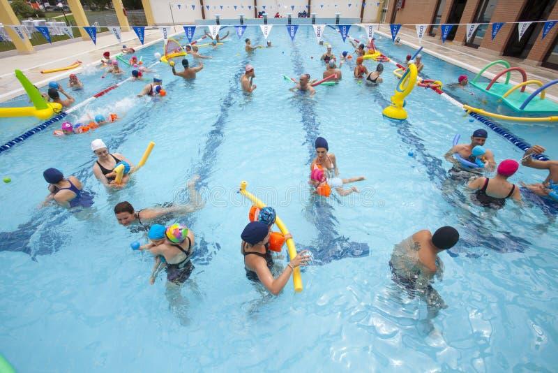 Pool met kinderen en ouders in water het spelen De pret van de familie royalty-vrije stock fotografie
