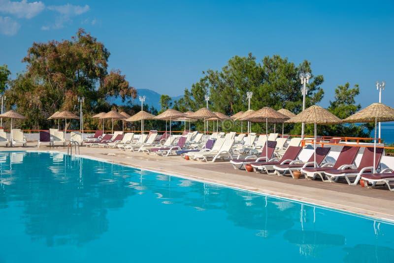 Pool mit sunbeds und Regenschirmen ist nahe dem Meer Konzept von Tourismus lizenzfreie stockfotos