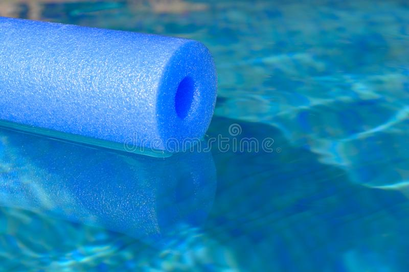 Blue pool noodle floating in a swimming pool, close up royalty free stock images