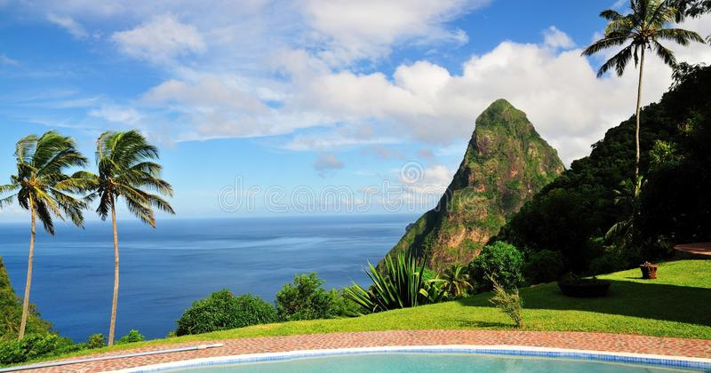 Pool, Palm Trees and Piton. Pool, Blue ocean, palm trees and clear blue sky, with a mountain know as Piton erected from the sea, summons the ambiance found in royalty free stock image