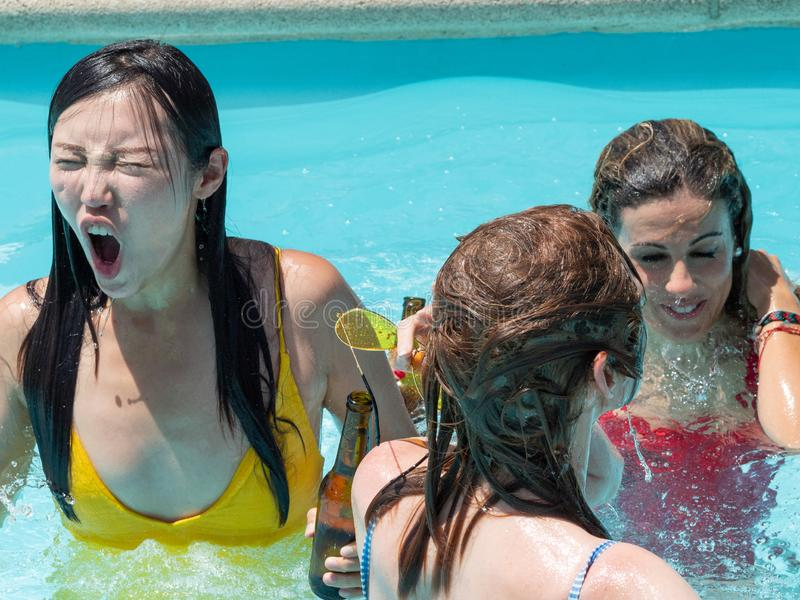 Pool party with beer. Multiracial people, black boy and Caucasian, Chinese and Russian girls stock photo