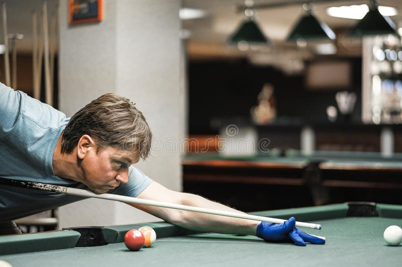 A pool player takes aim at the ball stock image