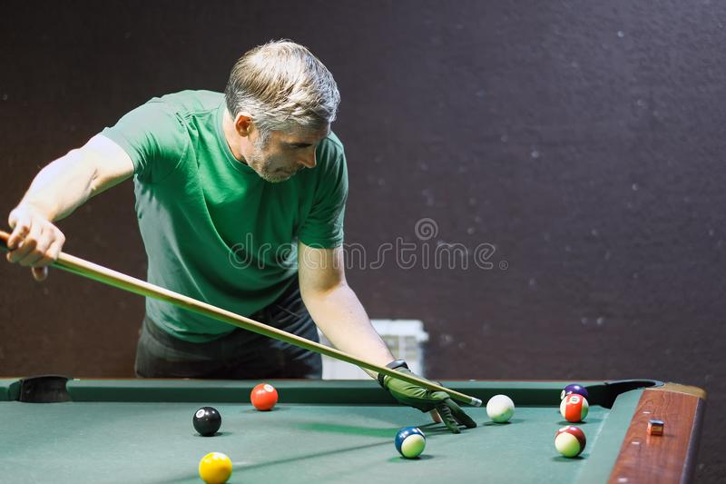 A pool player takes aim at the ball stock photo