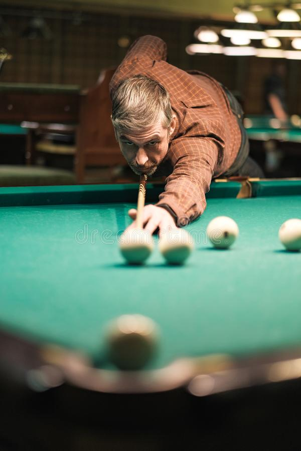 A pool player takes aim at the ball stock photography