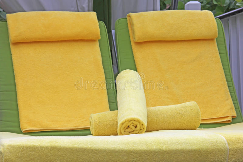 Pool side lounge chairs with yellow towels stock photos