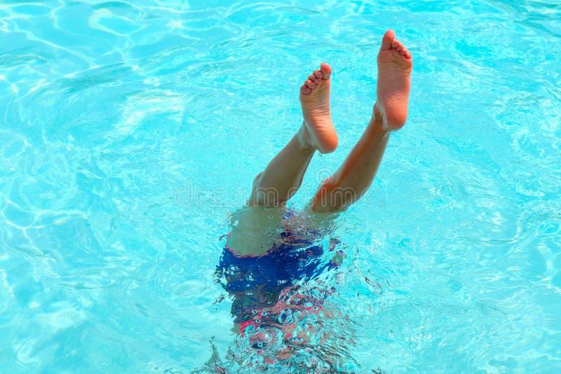 Pool-Spaß-Junge-Mädchen ist Füße oben für ihre Wasser-Akrobatik lizenzfreies stockbild