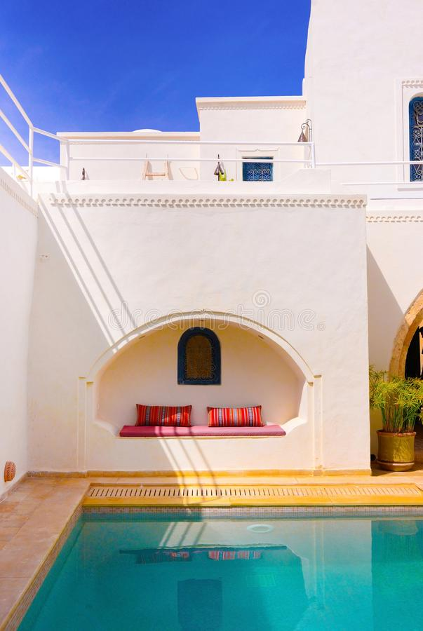 Pool Terrace, Exotic Destination, Arabic Decoration, Travel Tunisia. White building with enclosed pool terrace. Stripes shadows wall pattern. Bench with semi royalty free stock photos