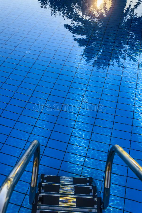pool trappasimning Sol på vatten för blå himmel: reflexion av solnedgången mellan palmträd på yttersidan av pölen arkivbilder