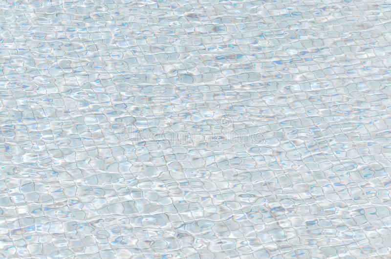 Pool water with waves and reflections of the floor tiles on water. Texture of tiles and sun reflection on the pool water stock images