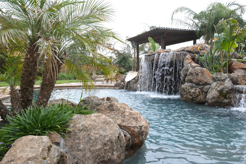 A pool with a waterfall in a luxury backyard royalty free stock photo