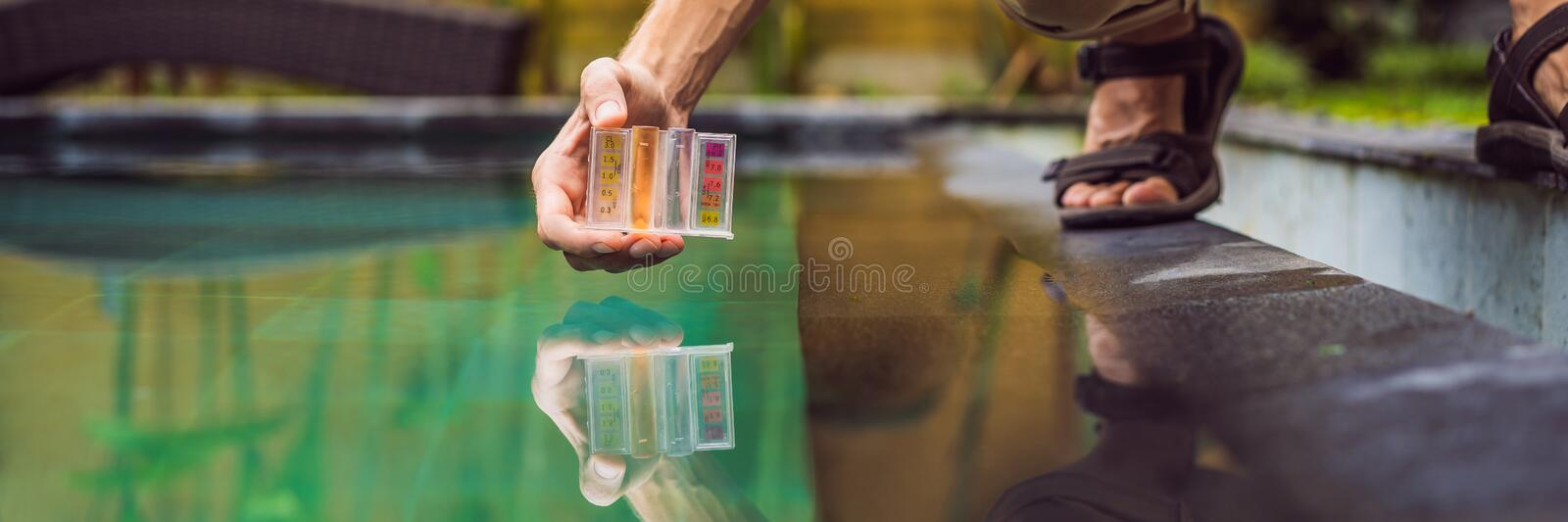 Pool worker checks the pool for safety. Measurement of chlorine and PH of a pool BANNER, LONG FORMAT stock image