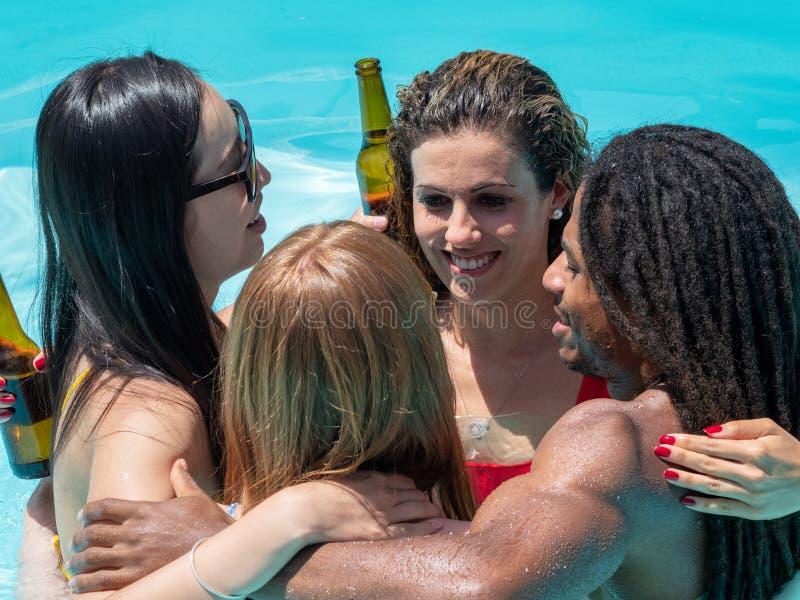 Poolpartij met bier Multiraciale mensen, zwarte jongen en Kaukasische, Chinese en Russische meisjes stock foto