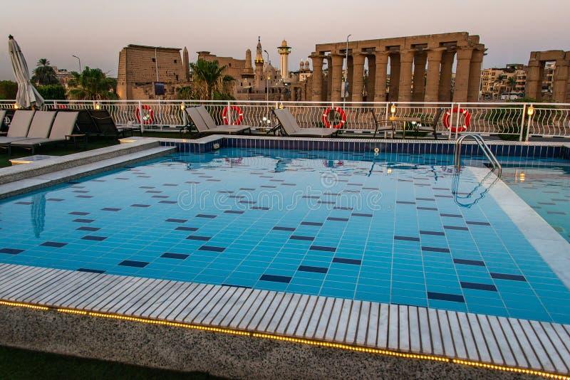 Poolplattform und Sonnenschirme des Luxusbootskreuzschiffs in ?gypten Luxor w?hrend des D?mmerungssonnenuntergangs lizenzfreie stockbilder