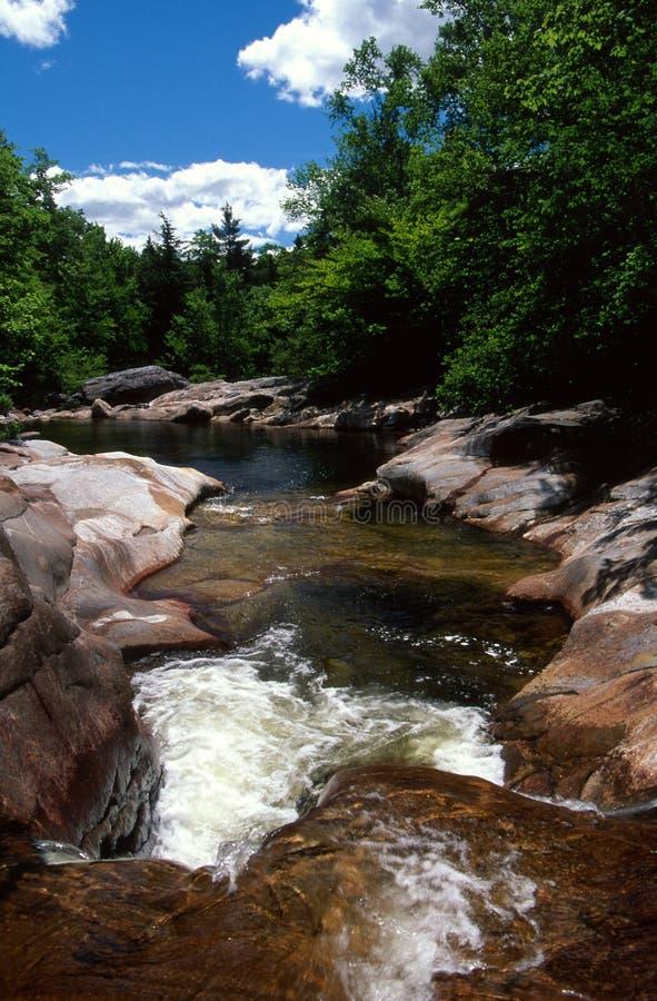 Pools, dalingen en geërodeerd graniet op een de zomerbeek stock fotografie