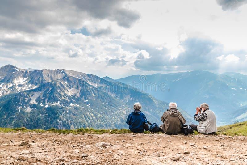 Poolse Tatras Polen 3 Juni 2019: de bejaarde mensen met rugzakken zitten op de grond hoog in de bergen Een oude mens kijkt royalty-vrije stock afbeelding