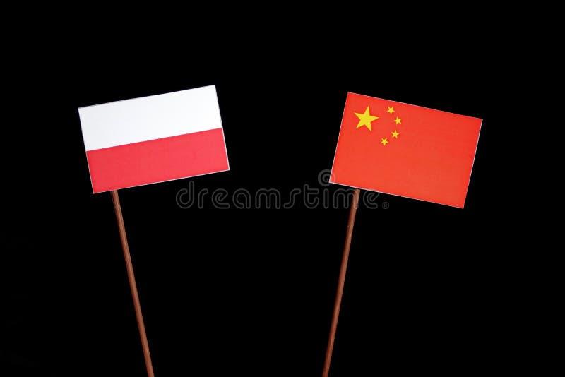 Poolse vlag met Chinese vlag op zwarte stock fotografie