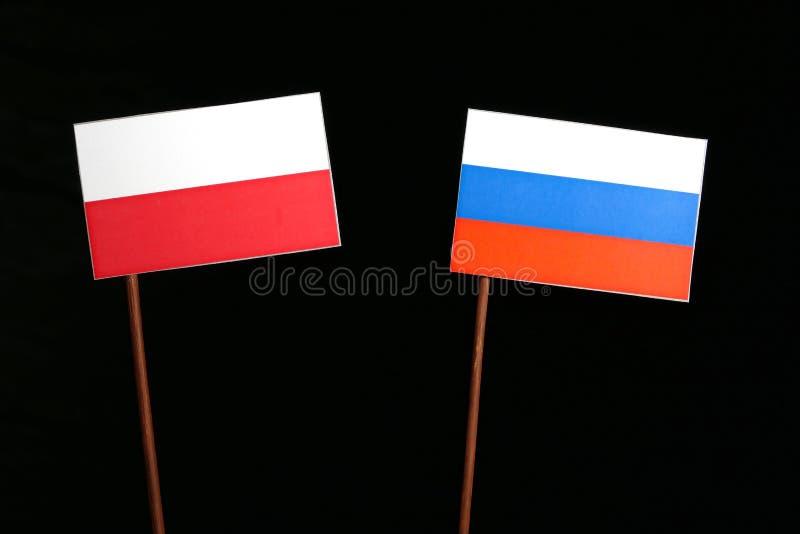 Poolse vlag met Russische vlag op zwarte stock foto's