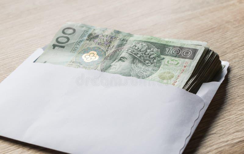 Poolse zloty munt honderd nota's in wit wikkelt op lijst C stock afbeeldingen