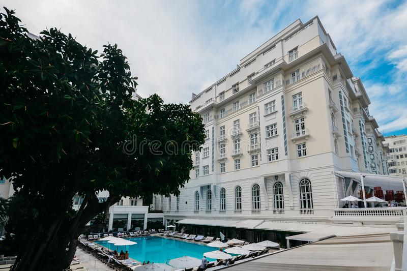 Poolside bar and lounge chairs at luxurious Copacabana Palace Belmond in Copacabana, Rio de Janeiro, Brazil. Rio de Janeiro, Brazil, March 17, 2019: Poolside bar royalty free stock photo