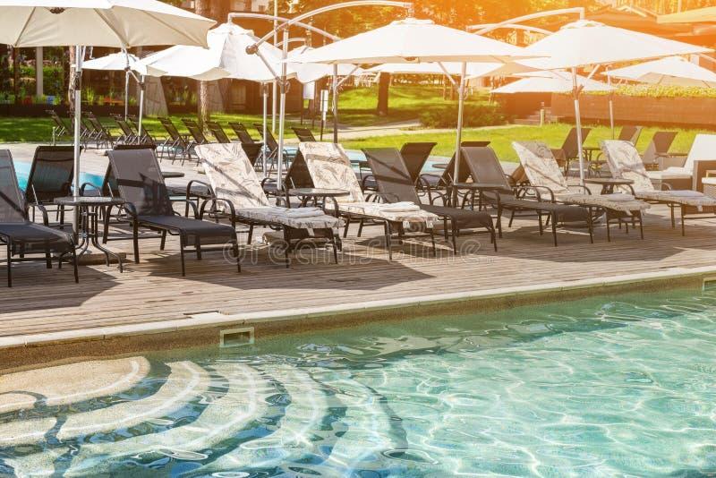 Poolside con chiare acqua blu e chaise-lounge sotto gli ombrelli su calore di giorno di estate Piscina alla località di soggiorno immagine stock