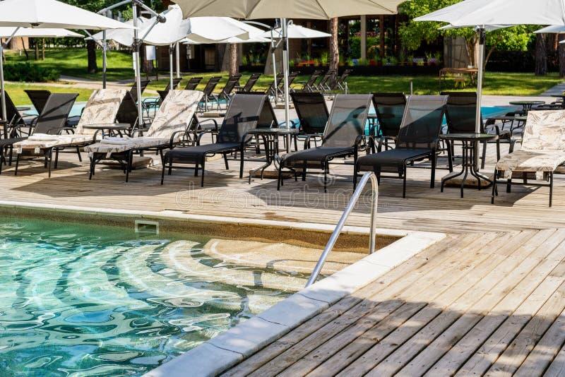 Poolside con chiare acqua blu e chaise-lounge sotto gli ombrelli su calore di giorno di estate Piscina alla località di soggiorno immagini stock libere da diritti